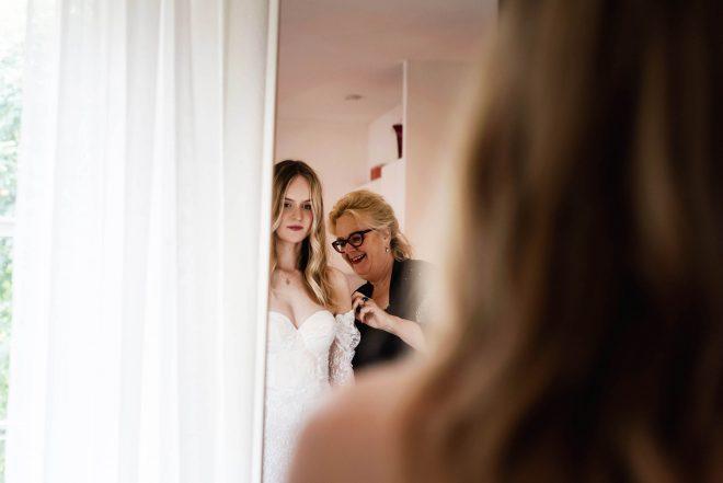 Carla werkt met een bruid aan een trouwjurk